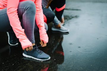 Man and woman getting motivated for a run in the winter rain