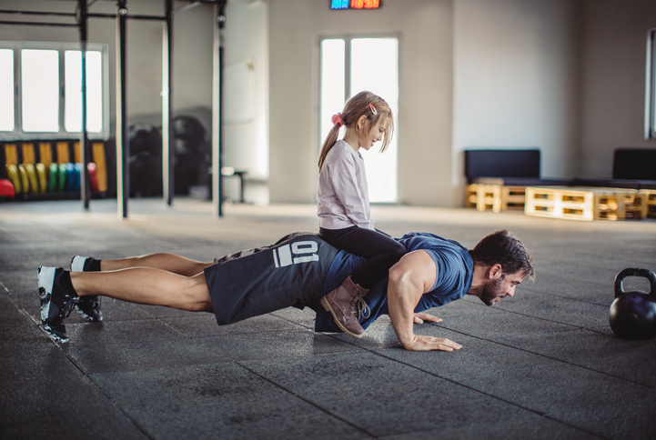 father doing pushups with daughter at his home gym in melbourne