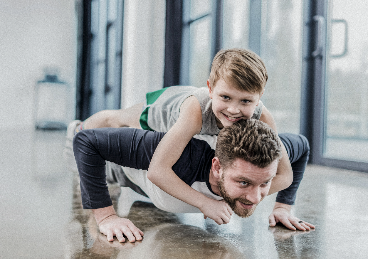 Parent doing pushups with son on his back